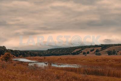 Одинокий рыбак в маленькой лодке на озере в облачной холмистой долине