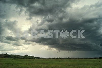 Storm cloud over green fields and hills