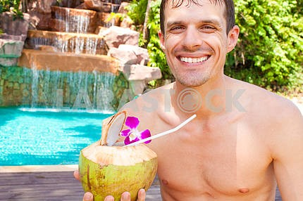 man drinking a cocktail by the pool