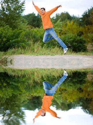 Happy Young Man - jumping in the sky against a green tree