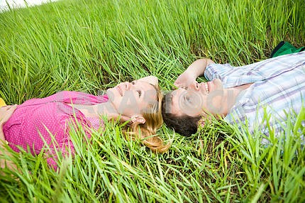 Young love couple lay on the green grass outdoors