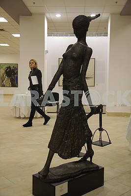 The girl passes by the sculpture