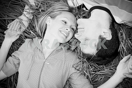 Young love couple lay on grass outdoors.