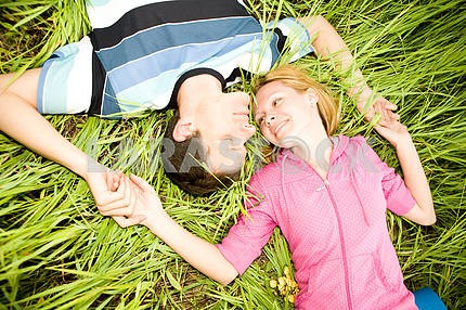 Young love couple lay on green grass outdoors