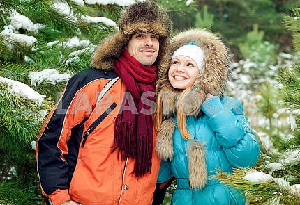 Young love Couple smiling against winter forest