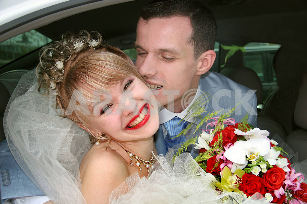 Couple on their wedding day kissing and laughing. In car. — Image 6778