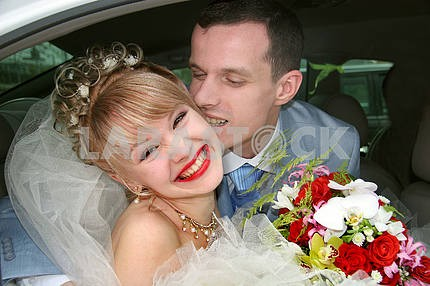 Couple on their wedding day kissing and laughing. In car.