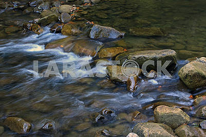 Stones and mountain river with small waterfall