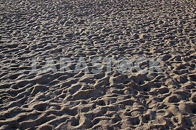 People trampled sand on the Mediterranean Sea beach