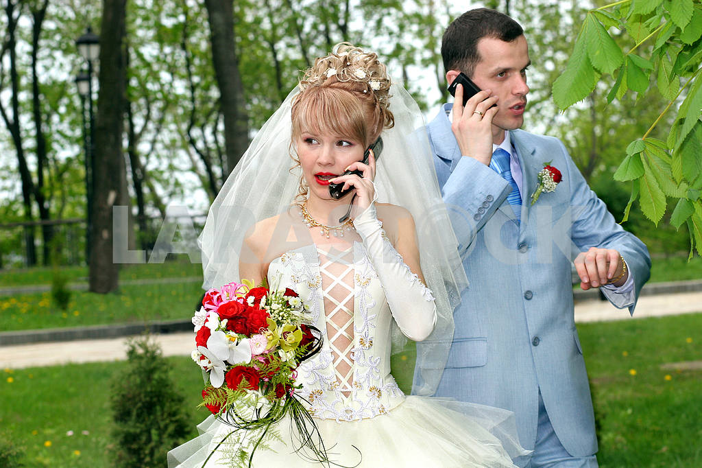 Bride and groom talk by phones — Image 6787