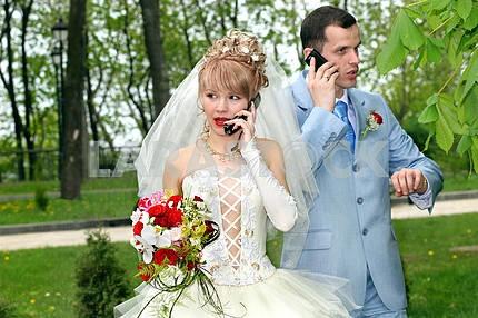 Bride and groom talk by phones