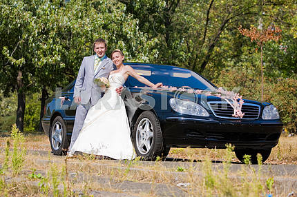 Groom and bride joy against backdrop wedding car decorated with