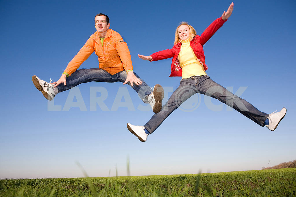 Happy smiling couple  jumping in sky — Image 6798