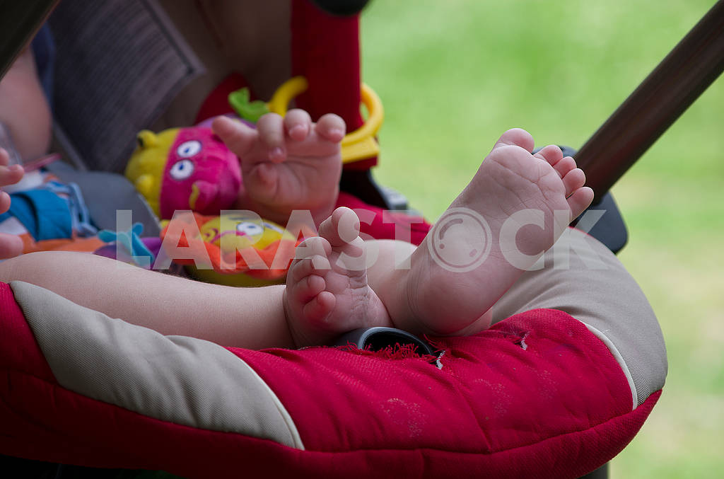 The child sits in a stroller with legs stretched up — Image 67985