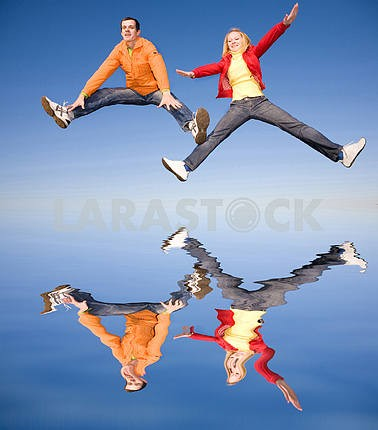 Happy smiling couple  jumping in sky. Reflected in water