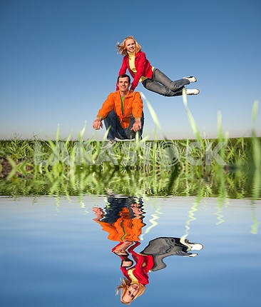 Happy smiling couple  jumping in blue sky. Reflected in Water.