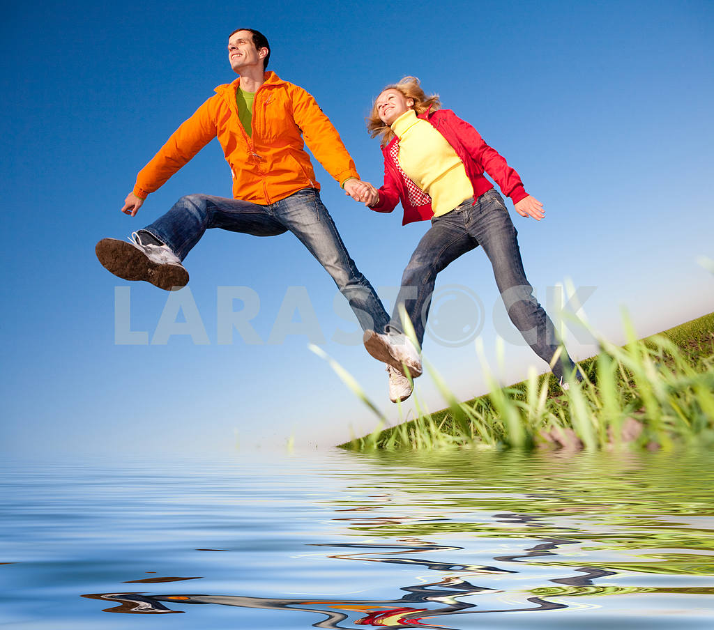 Happy smiling couple  jumping in sky above a green meadow. Refle — Image 6818