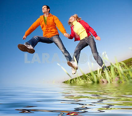 Happy smiling couple  jumping in sky above a green meadow. Refle