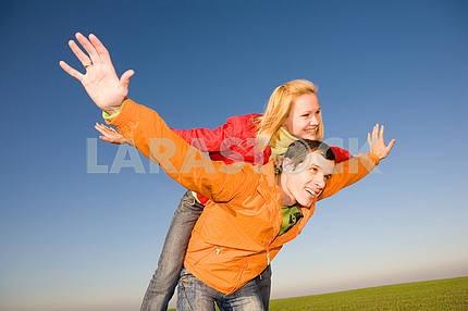 Молодые любви, пара , улыбаясь в голубое небо