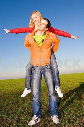 Счастливая пара улыбаясь прыжки в голубое небо