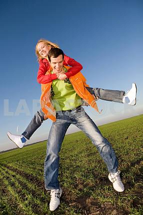 Счастливая пара улыбаясь прыжков в небе над зеленый луг