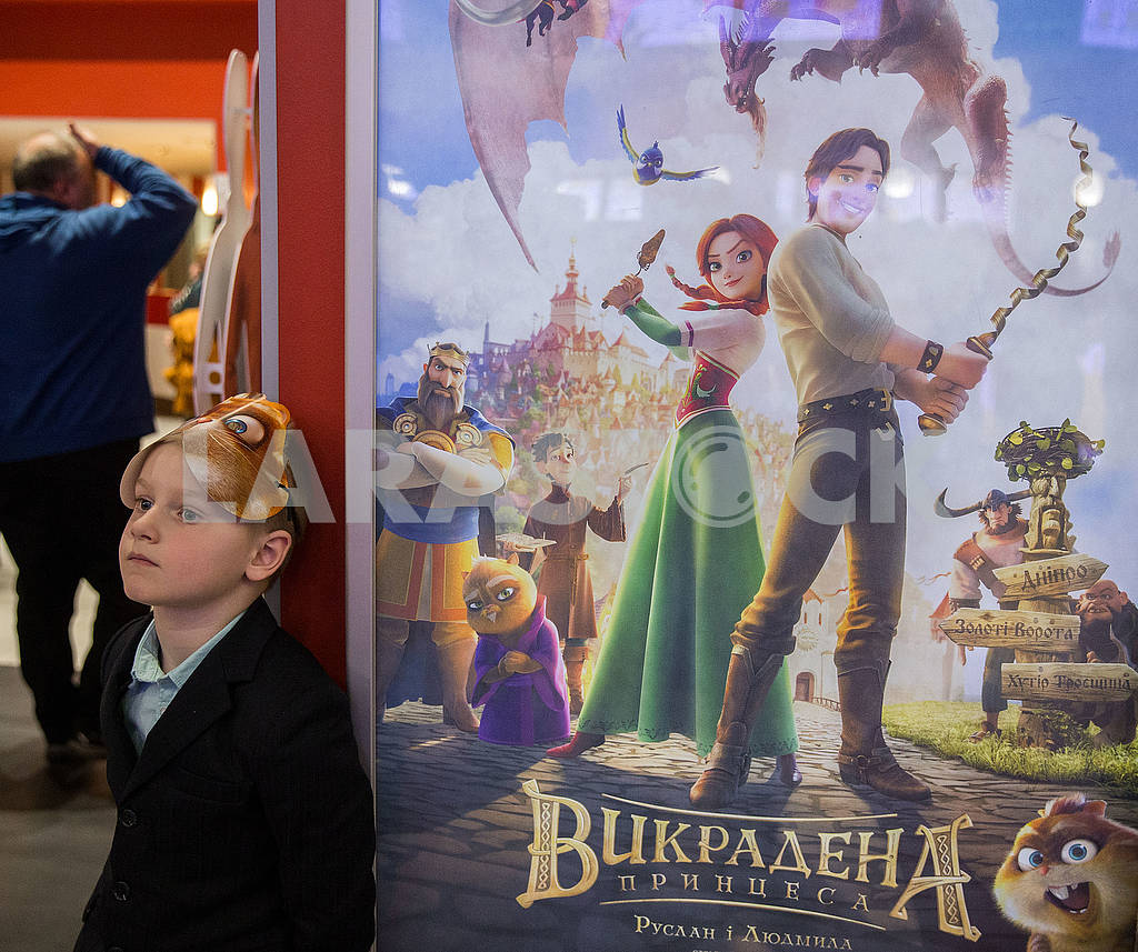 A boy in a mask near a poster — Image 69140