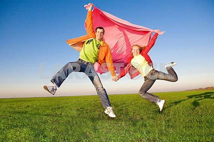 Счастливая молодая пара прыгает в небо над зеленый луг