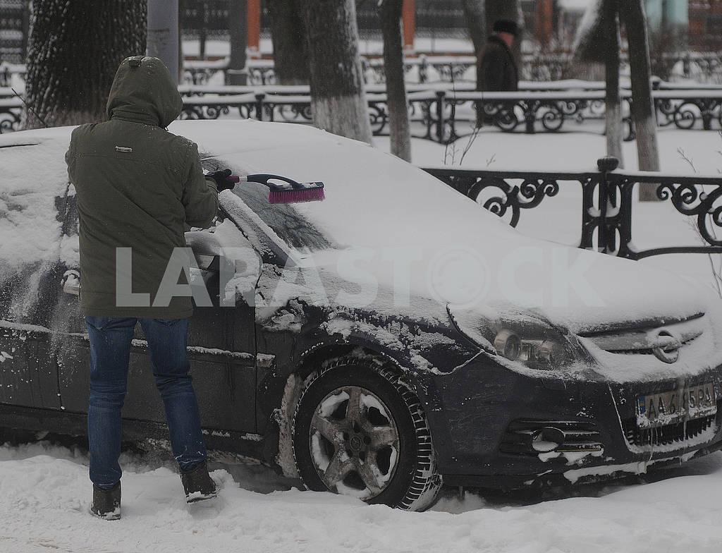 Мужчина чистит свой автомобиль от снега, — Изображение 69169