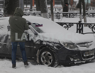 A man is cleaning his car from snow,