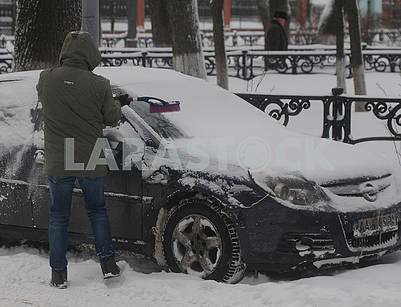 Мужчина чистит свой автомобиль от снега,