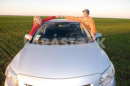 Счастливая молодая пара с нового автомобиля
