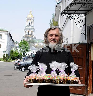 Священник держит пасхальные куличи