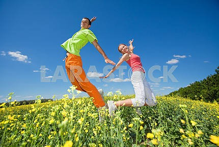 Young love Couple jumping under blue sky