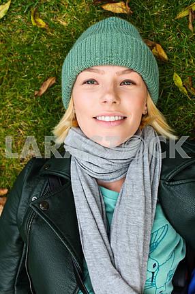 Красивая девушка лежит на траве и улыбается