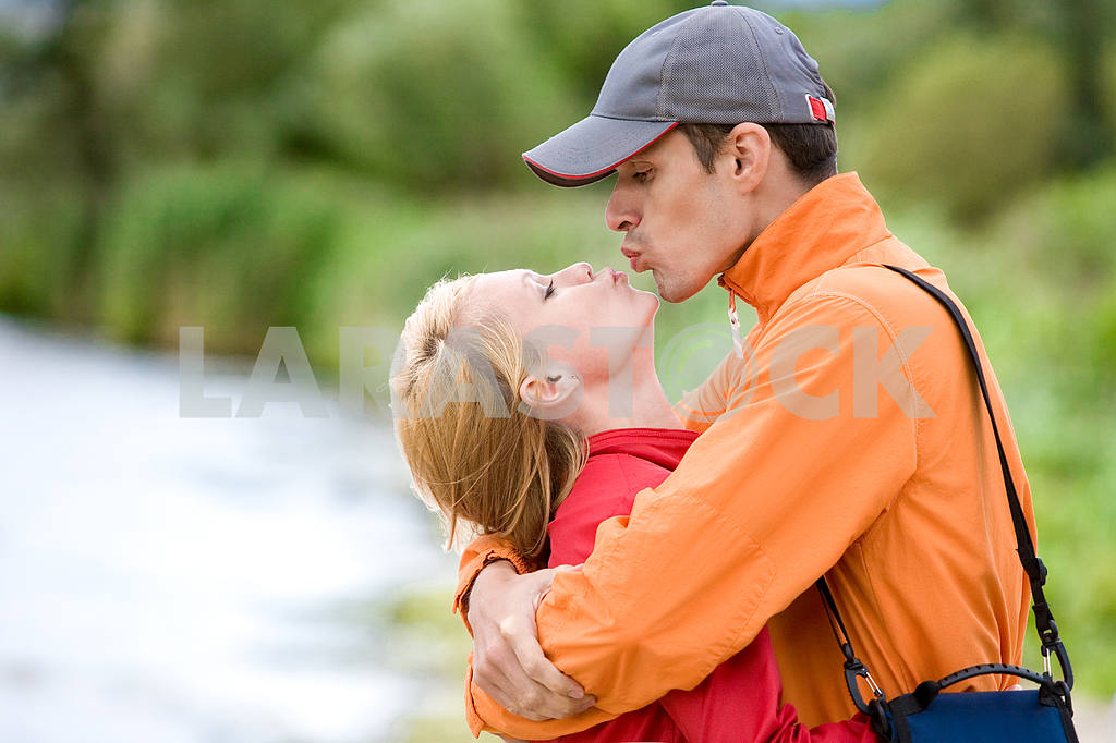 Молодые любви пара поцеловал на берегу реки — Изображение 7004