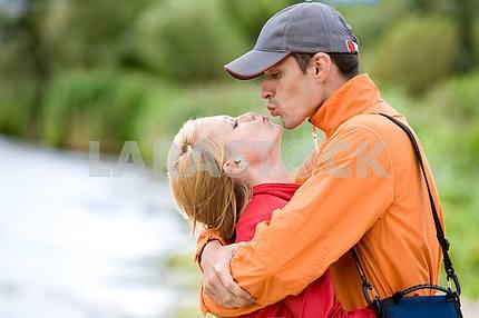 Молодые любви пара поцеловал на берегу реки