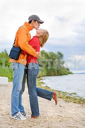 Молодые любви пара поцеловал на берегу реки .