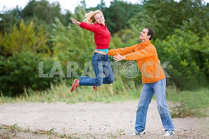 Happy Young Couple - jumping against a green tree