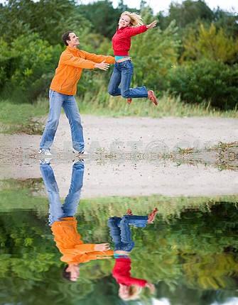 Счастливый молодая пара - прыжки на зеленой дерева