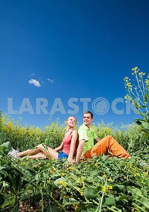 Молодые любви пара весело в поле под голубым небом