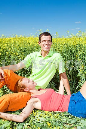 Young love couple relaxing while lying on grass