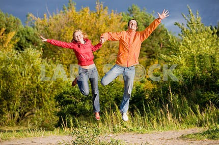 Happy Young Couple - jumping in the sky above a orange-green tre