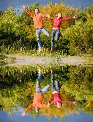 Счастливый молодая пара - прыжки в небо над оранжево- зеленый Tre