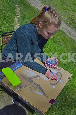 Молода дівчина малює на пленері