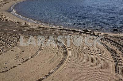 Очищений трактором пісок на пляжі Середземного моря