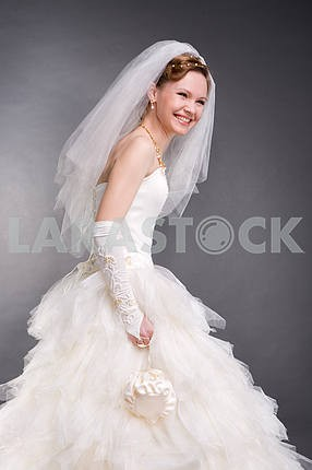 Smiling bride in the studio. In white dress. Isolated over black
