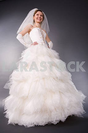 Smiling bride in the studio. In white dress. In all growth. Isol