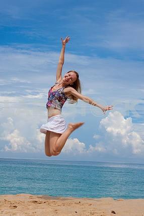 Счастливый молодая женщина прыгает на фоне лазурного моря
