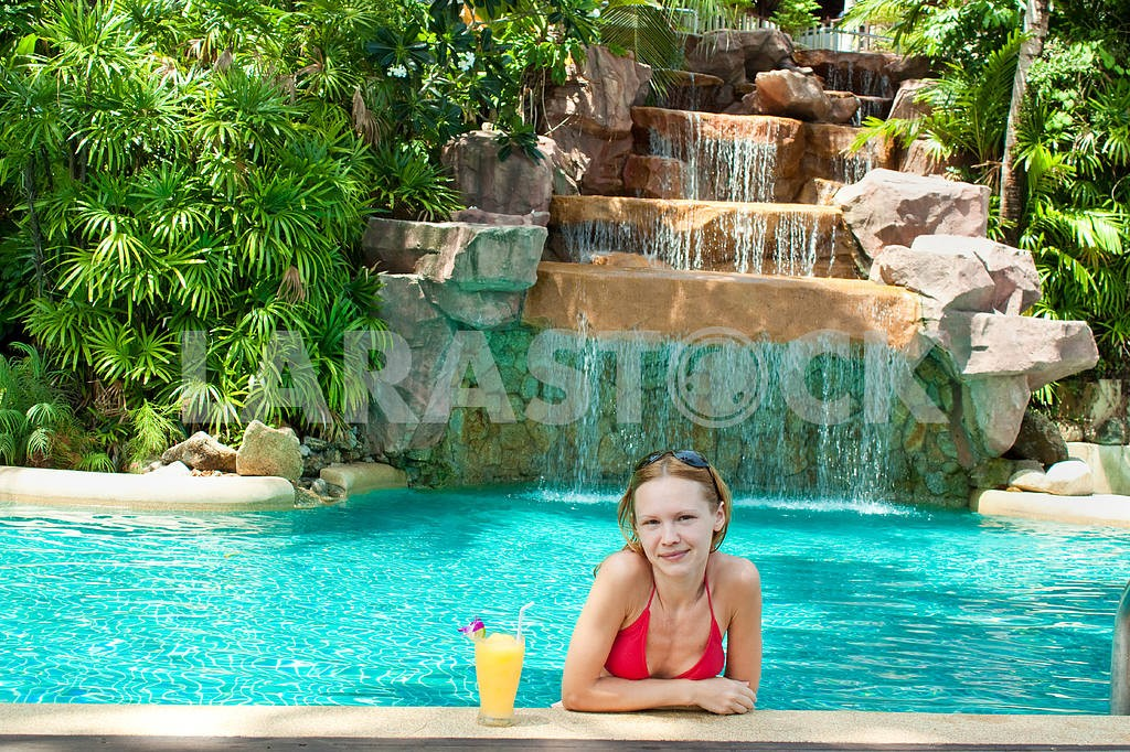 Happy young woman with an exotic cocktail in the pool — Image 7100