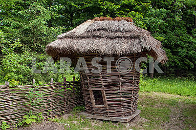 Traditional  corn drier shed for storing corn cobs in a peasant